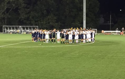 Players from both Cal U and Cedarville gather in the center of the field after the game to pray.