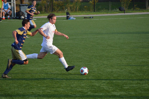 Elliot Taylor, senior, pushes up the field and past Pitt-Johnstown's defenders.