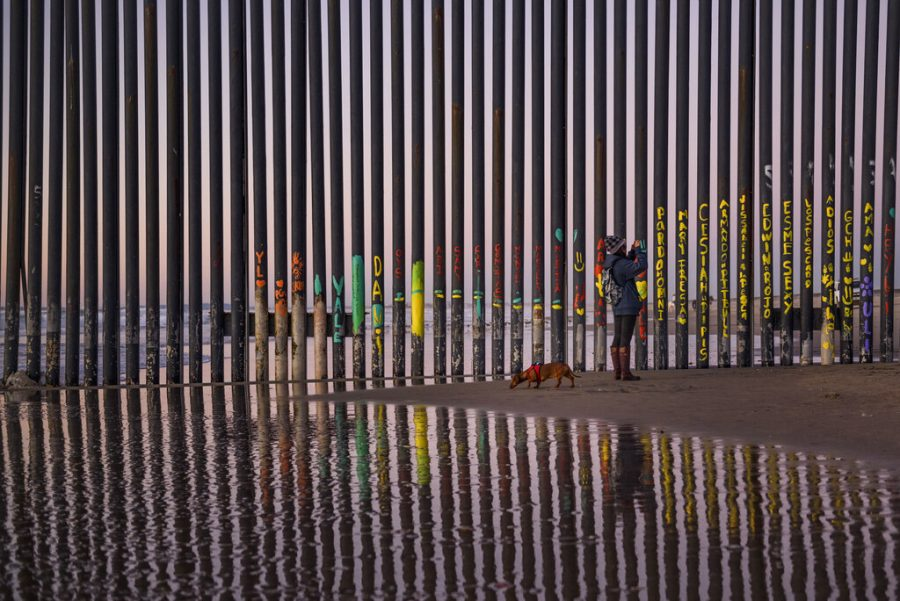 A+Woman+walking++her+dog+takes+a+Photograpoh+of+the+border+fence+that+seperates++San+Diego%2C+CA+and+Tijuana%2C+Mexico+