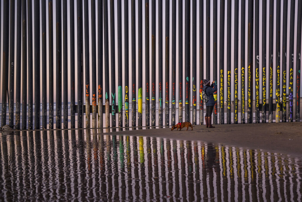 A Woman walking  her dog takes a Photograpoh of the border fence that seperates  San Diego, CA and Tijuana, Mexico