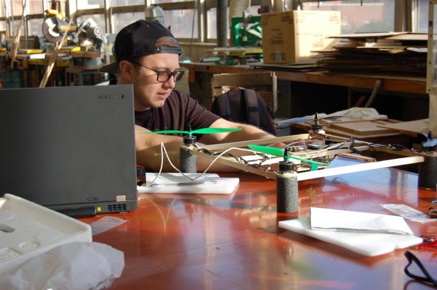 A college student prepares an unmanned aerial system for flight.