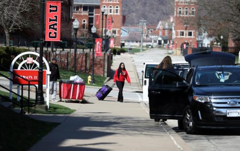 Alyssa Emerson, freshman,  Aliquippa, Pa. pulls a suitcase and is met by her parents, Marvin and Felisa Emerson, as she moves out of Johnson Hall on March 22, 2020.