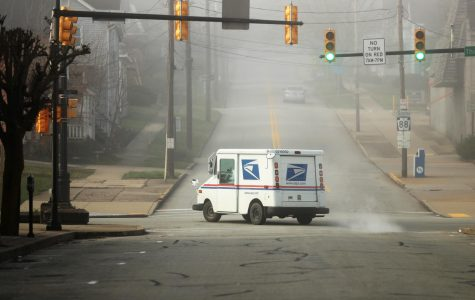 A U.S. Postal Service truck at the intersection of Third and Wood Street, California, Pa.  March 26, 2020