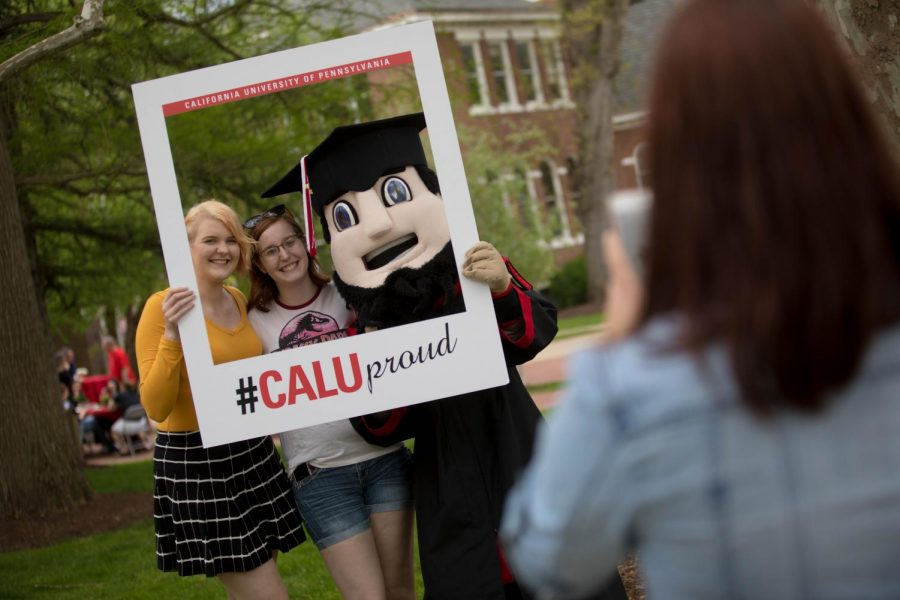 Students pose for a photo with mascot Blaze at the Cal U Commencement, May 11, 2018.