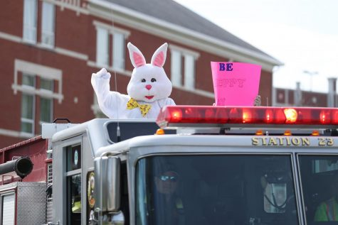 The Easter Bunny waves to kids from the top of the fire truck while riding past Dixon Hall on Saturday, April 11, 2020.