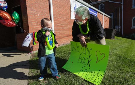 Clark Harrison, chairman, holds a welcome sign and greets Weston Bourne upon arrival at The Village Early Childhood Education Center, Liberty Street, California, Pa., on June 1, 2020.  Prior to opening day, children were invited to select and vote on hair colors for the staff and administration.  They selected the color