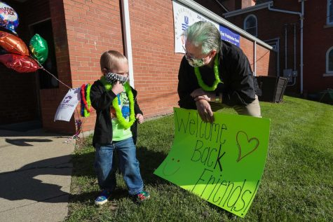 "Clark Harrison, chairman, holds a welcome sign and greets Weston Bourne upon arrival at The Village Early Childhood Education Center, Liberty Street, California, Pa., on June 1, 2020.  Prior to opening day, children were invited to select and vote on hair colors for the staff and administration.  They selected the color ""green"" for Harrison."