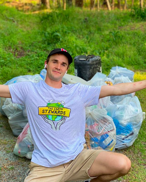 Daniel Toben poses with trash collected from plogging, an activity that is a combination of jogging and picking up roadside litter.