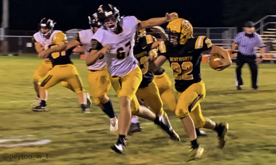 Bentworth Senior Owen Petrisek (#22, black) runs the ball while junior Elijah Smith (#67, white) tries to take him down.