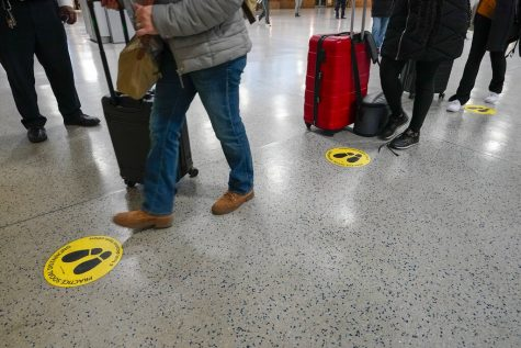 Yellow dots mark the spots for proper social distancing as travelers line up to board an Amtrak train , Tuesday, Nov. 24, 2020, in New York