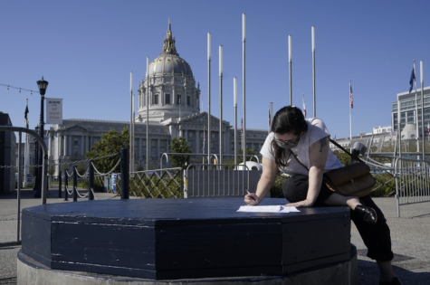 Andie Grossman fills out her ballot before delivering it to a San Francisco Department of Elections voting center in San Francisco, Sunday, Nov. 1, 2020.