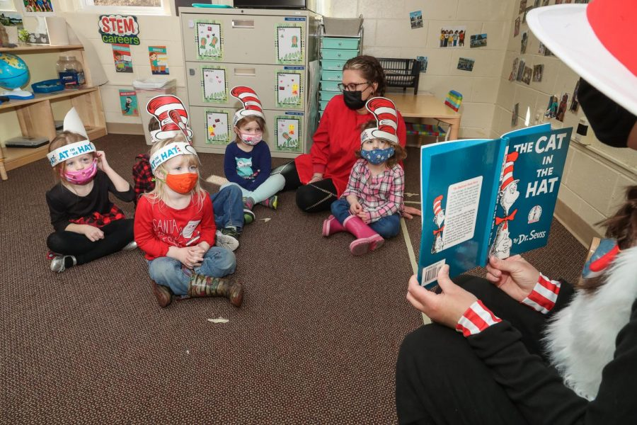 Children in Miss Darcy's room gather around as Ashley Roth, director, presents a reading of