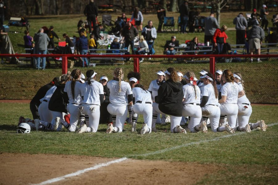 Cal U softball team gathers for a post-game discussion with the coaching staff.