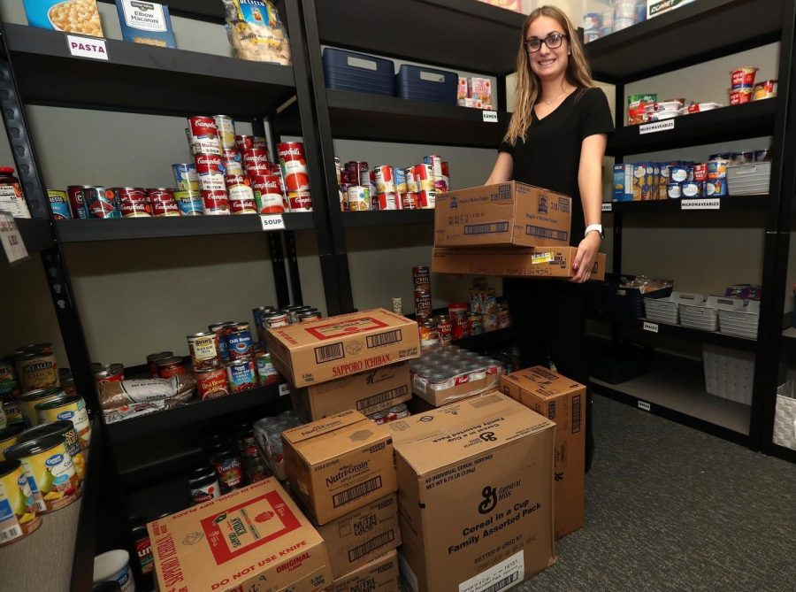 Student Miranda Anderson poses with boxes of food at the Cal U Cupboard.