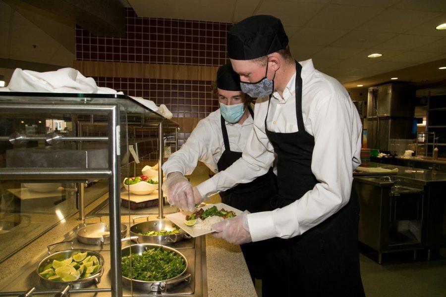 Nolan Bistline (on right) and Brendan Halpin, junior PGM students, prepare  to serve a dish of beef broccoli stir fry.