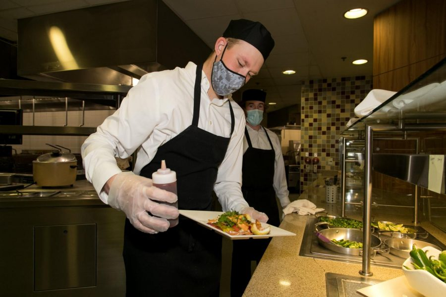 Cal U Professional Golf Management (PGM) students Nolan Bistline (on left) and Brendan Halpin prepare to serve a plate of orange chicken stir fry in the Gold Rush dining hall, Natali Student Center, April 21. 2021.