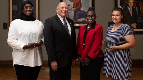 Interim University President Bob Thorn and Shelta Camarda-Webb, Interim Chief Diversity, Equity and Inclusion Officer, present Fatouma Keita, left, with the Jennie Carter Distinguished African American Student Award and Kimberly Melck, right, with the Jan Zivic Outstanding LGBTQ+ Leadership Award.
