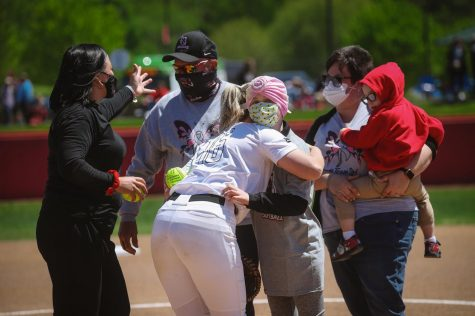 Cal U softball catcher Brooke Wilson hugs 11-year-old Olivia Sealy after throwing the first pitch at the Cal U softball game at Lilley Field on May 1, 2021.