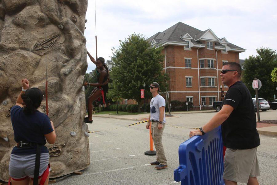 ROTC) Instructors teach students to climb the wall.