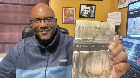Dr. Todd Carlisle, associate professor of Journalism in the Department of Culture, Media, and Performance, California University of Pa. holds a copy of his novel The Souls of Clayhatchee